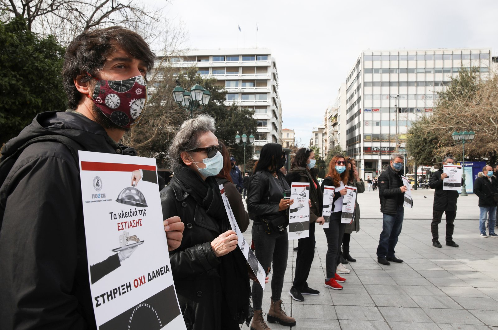 Restaurant and cafe owners hold placards during a protest over lockdown measures that have kept their businesses closed, amid the spread of the coronavirus disease (COVID-19), in Athens, Greece, Feb. 10, 2021. (Reuters Photo)
