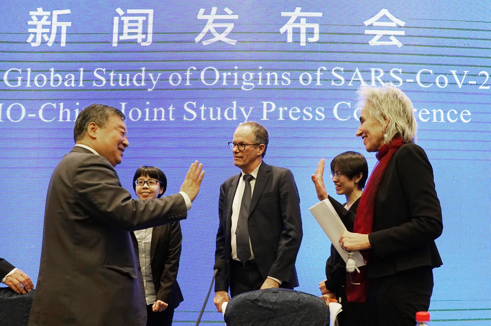 Members of the World Health Organization (WHO) team Marion Koopmans (R) and Peter Ben Embarek say farewell to their Chinese counterpart Liang Wannian (L), after a WHO-China Joint Study Press Conference held at the end of the WHO mission in Wuhan, China, Tuesday, Feb. 9, 2021. (AP Photo)