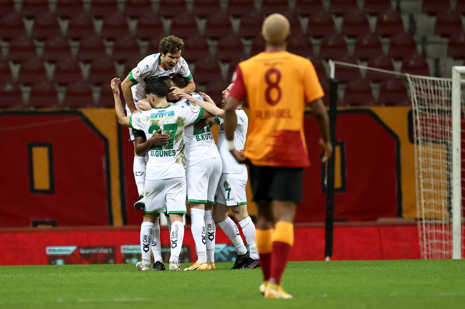 Alanyaspor players celebrate after a goal while Galatasaray's Ryan Babel walks during the Turkish Cup match at the Turk Telekom Stadium in Istanbul on Feb. 10, 2021 (AA Photo)