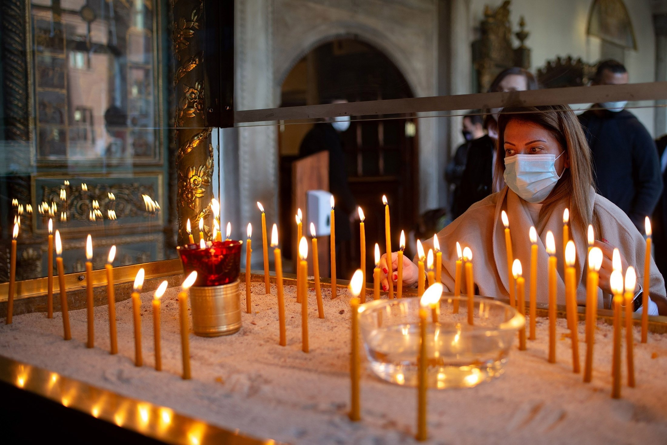 An Orthodox worshipper lights a candle during the Epiphany celebrations at the Patriarchal Church of Saint George amid the spread of COVID-19, in Istanbul, Turkey, Jan. 6, 2021.