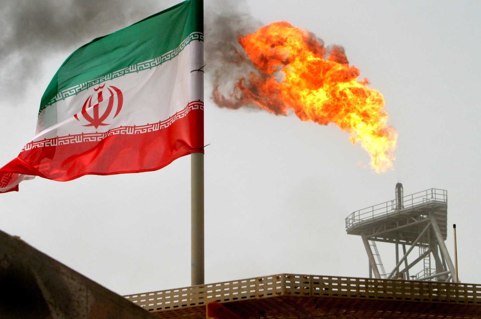 A gas flare on an oil production platform in the Soroush oil fields is seen alongside an Iranian flag in the Persian Gulf, Iran, July 25, 2005. (Reuters Photo)