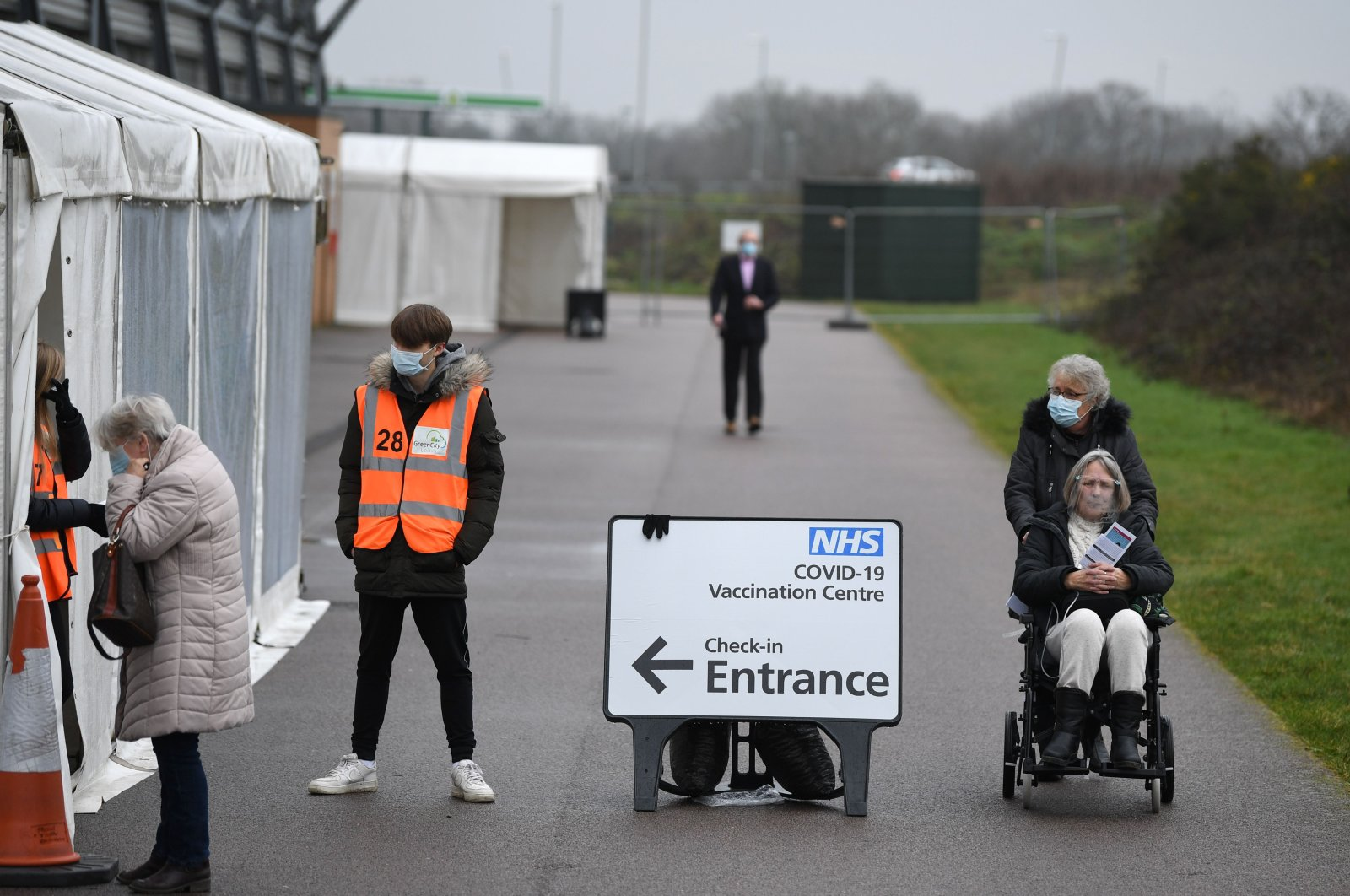 Volunteers assist a woman (L) as people who received a COVID-19 vaccine leave a temporary vaccination hub set up at the Colchester Community Stadium in Colchester, Essex, southeast England, Feb. 6, 2021. (AFP Photo)