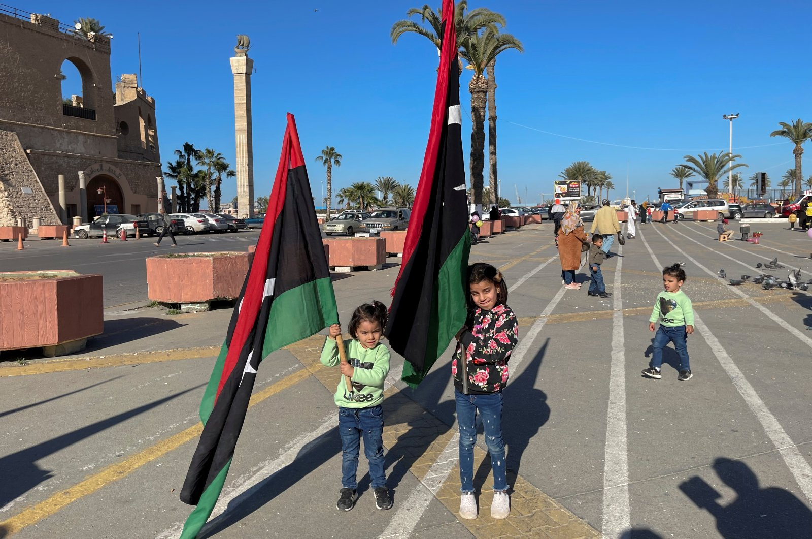 Children carrying Libyan flags pose for photos at Martyrs' Square in Tripoli, Libya, Feb. 5, 2021. (REUTERS Photo)