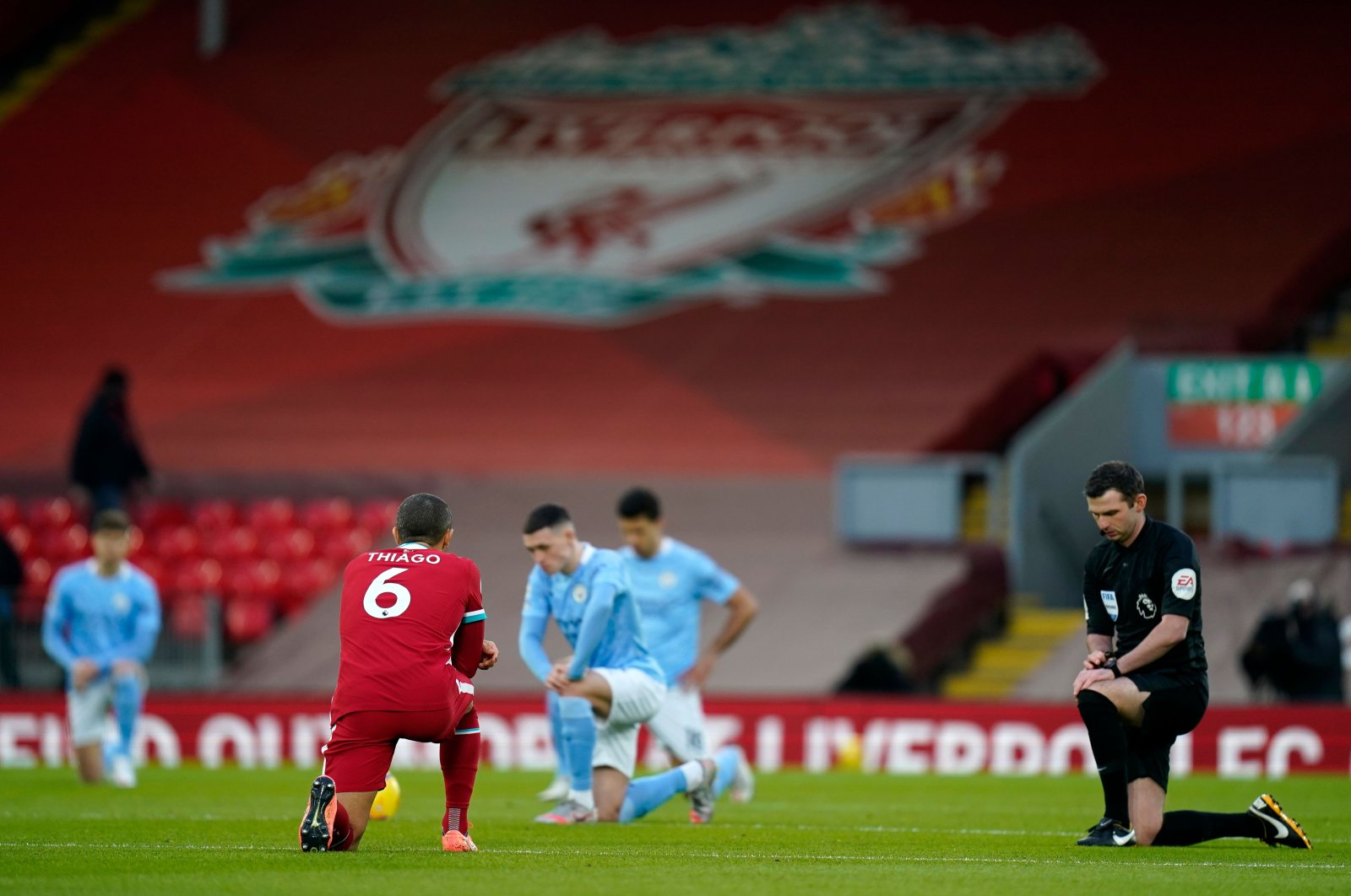 """English referee Michael Oliver (R) and players """"take a knee"""" in support of the No Room For Racism campaign ahead of a Premier League match between Liverpool and Manchester City at Anfield in Liverpool, England, Feb. 7, 2021. (AFP Photo)"""