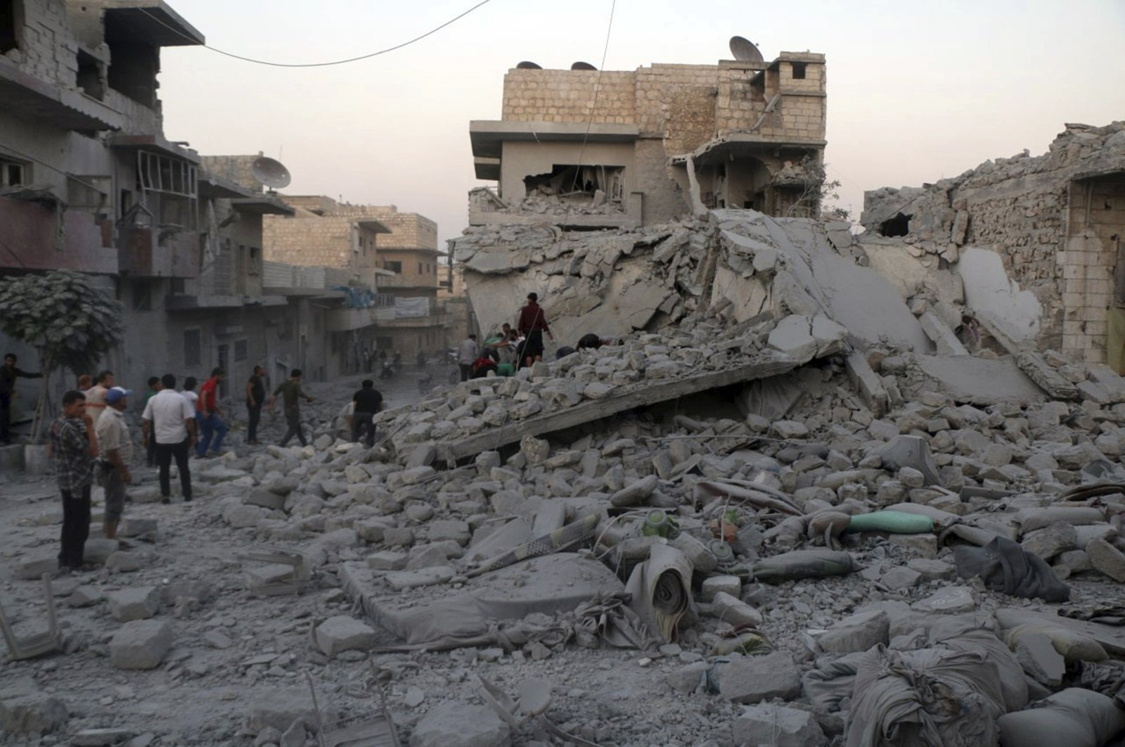 This photo released by the opposition Syrian Civil Defense rescue group, also known as White Helmets, which has been authenticated based on its contents and other AP reporting, shows people searching for victims under the rubble of destroyed buildings that were hit by airstrikes in the northern town of Maaret al-Numan, in Idlib province, Syria, Aug. 28, 2019. (AP Photo)