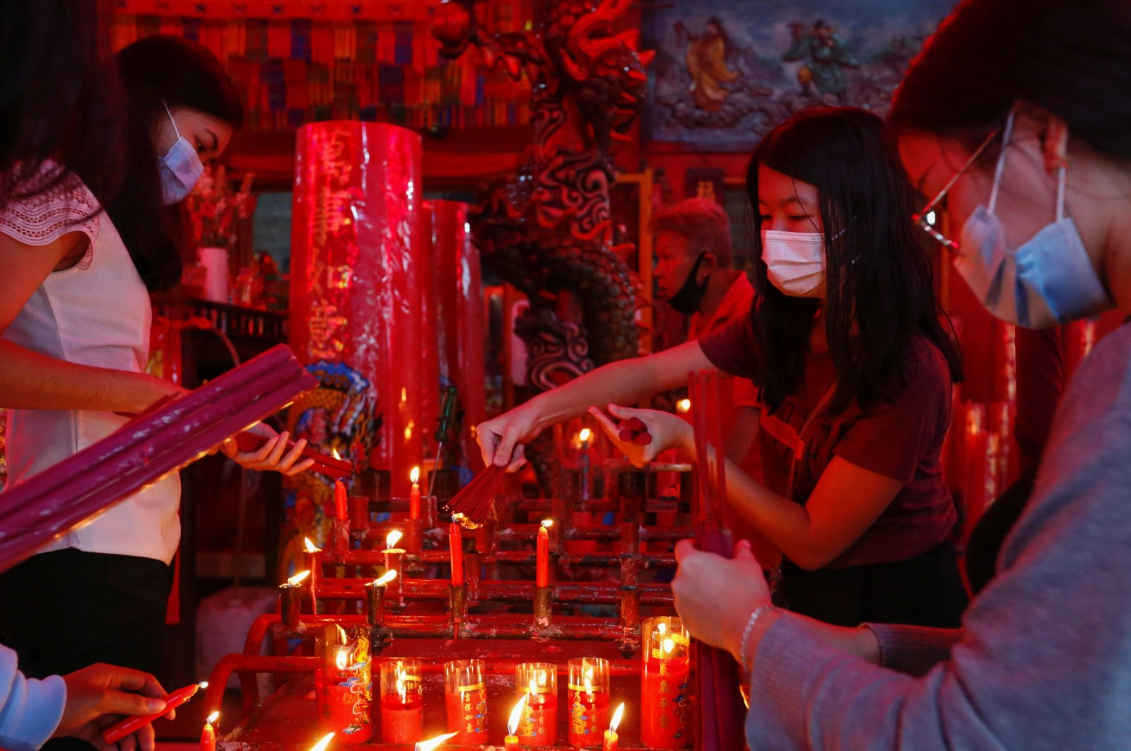 Worshippers wearing protective masks light incense sticks as they pray during Chinese Lunar New Year's eve at a temple in Jakarta, Indonesia, Feb. 11, 2021. (Reuters Photo)
