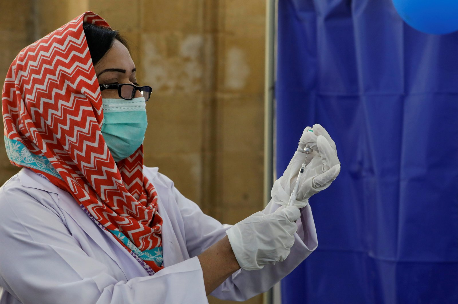 A paramedic prepares a dose of Sinopharm's coronavirus disease (COVID-19) vaccine before administering it to a health worker at a vaccination center in Karachi, Pakistan, Feb. 11, 2021. (REUTERS/Akhtar Soomro)