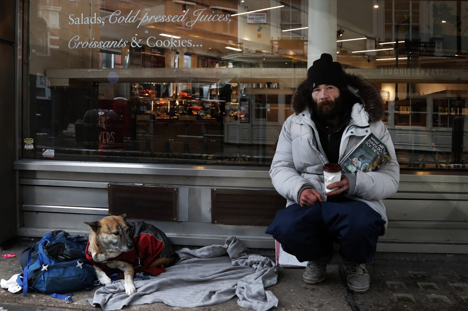 A homeless person and his dog rest outside a coffee shop in London, Feb. 8, 2021. (AP Photo)