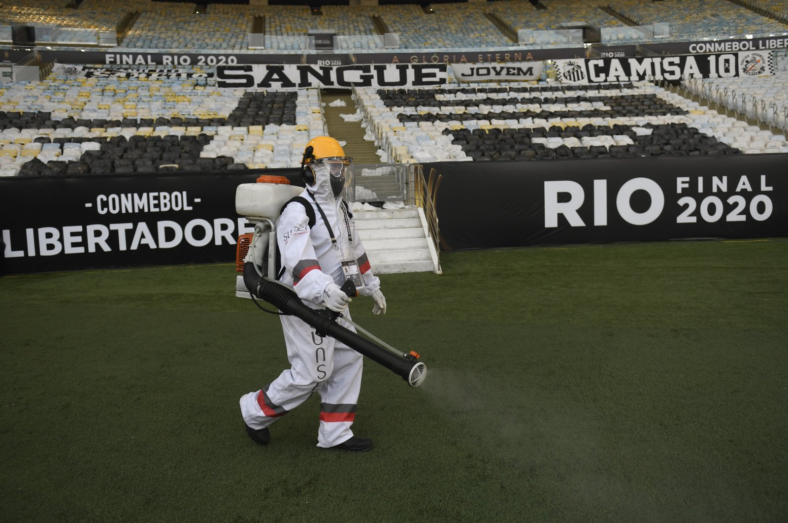 A worker wearing protective gear disinfects the pitch as a precaution against the coronavirus during the half break of a Copa Libertadores final soccer match between Brazil's Palmeiras and Brazil's Santos at the Maracana stadium in Rio de Janeiro, Brazil, Jan. 30, 2021. (AP Photo)