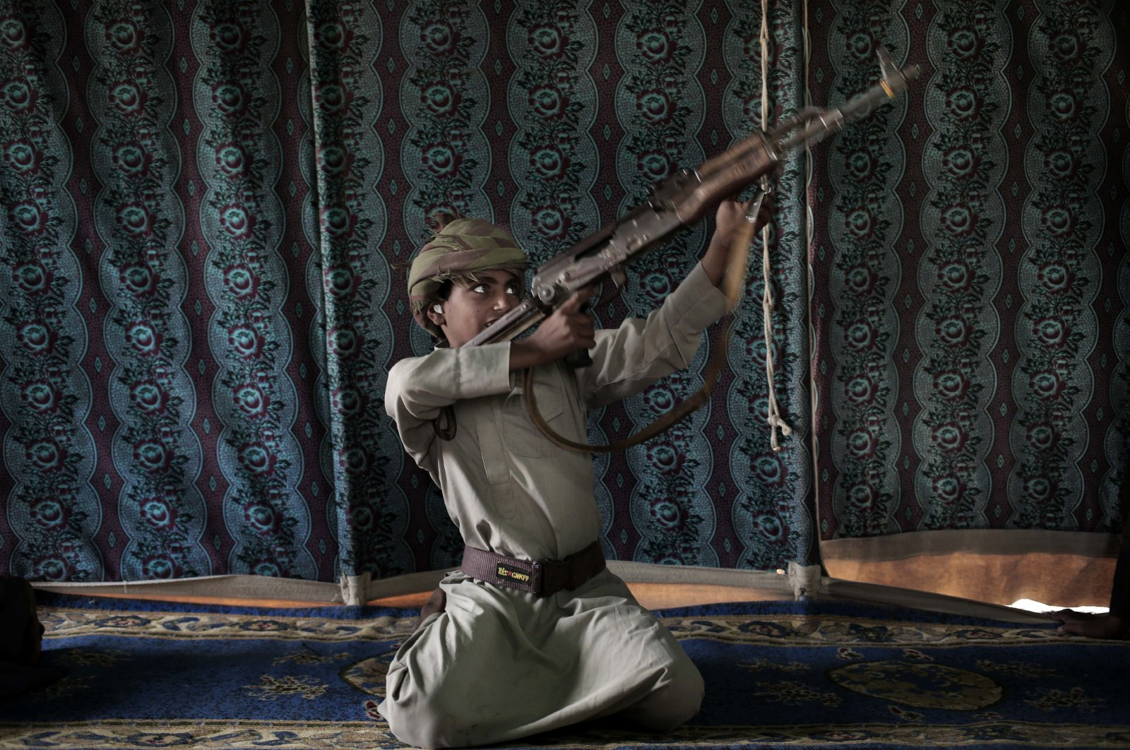 Kahlan, a 12-year-old former child soldier who fought alongside Houthi rebels, demonstrates how to use a weapon at a camp for displaced persons where he took shelter with his family in Marib, Yemen, July 27, 2018. (AP Photo)