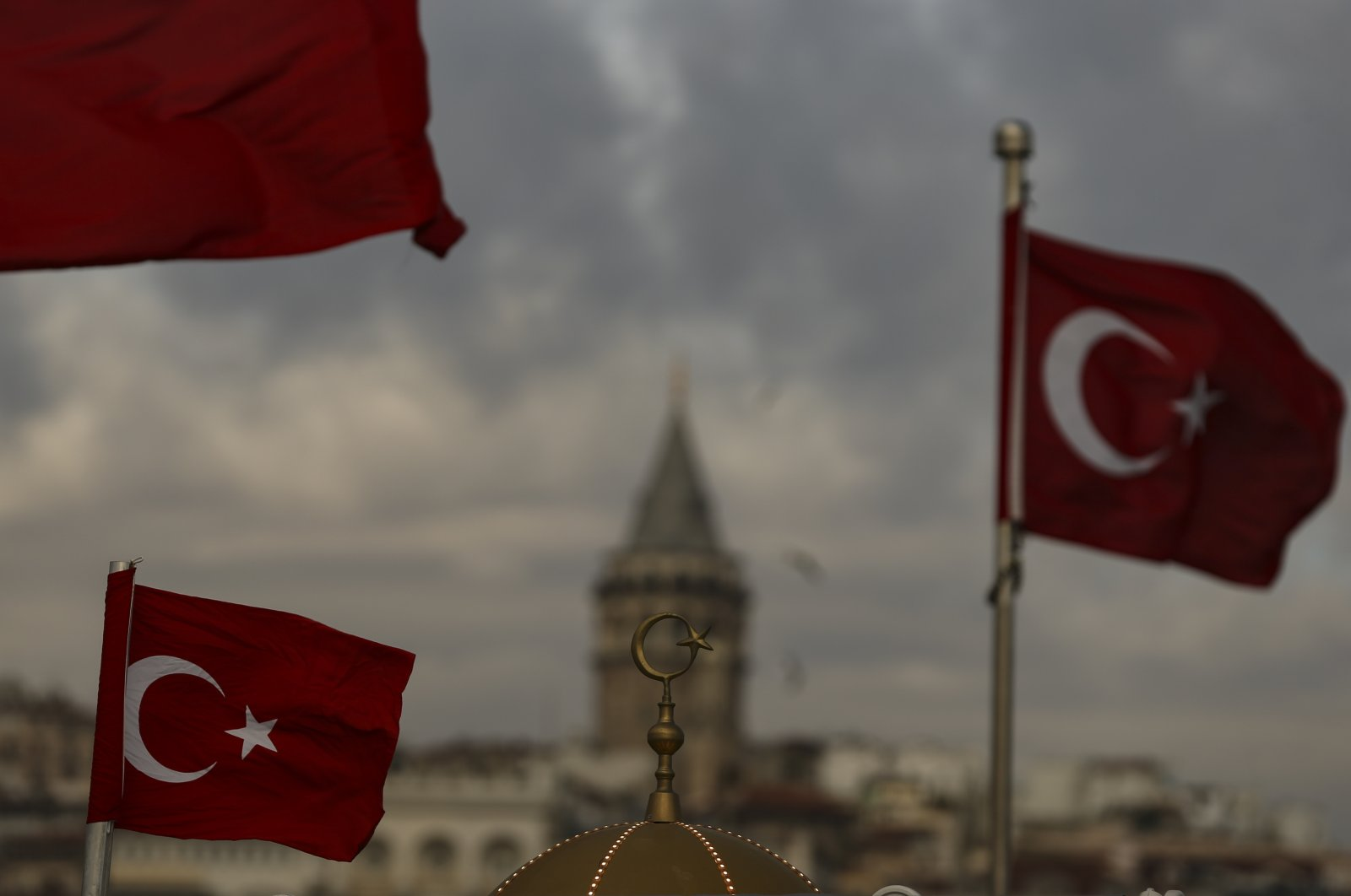 Turkish flags wave with the iconic Galata Tower in the background, hours before a two-day weekend lockdown, Istanbul, Turkey, Jan. 29, 2021. (AP Photo)