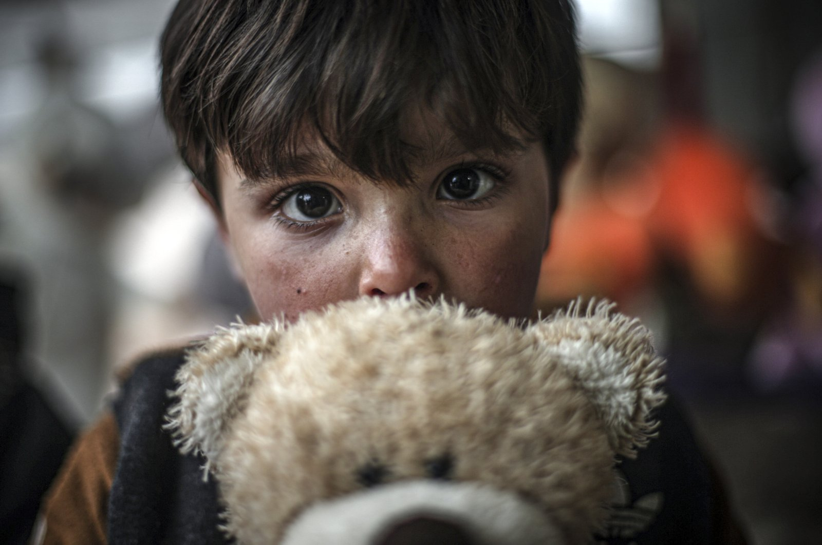 A Syrian child holds a teddy bear in front of a toy shop in northwestern Idlib province, Syria, Feb. 12, 2021. (AA Photo)