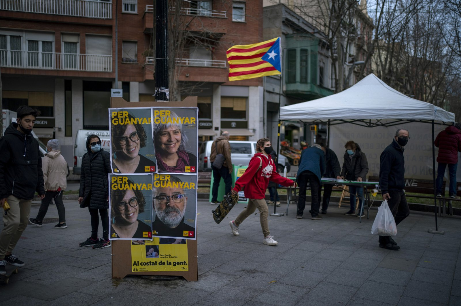 Pedestrians walk past electoral posters with portraits of candidates for the upcoming regional election in Barcelona, Spain, Jan. 30, 2021. (AP Photo)