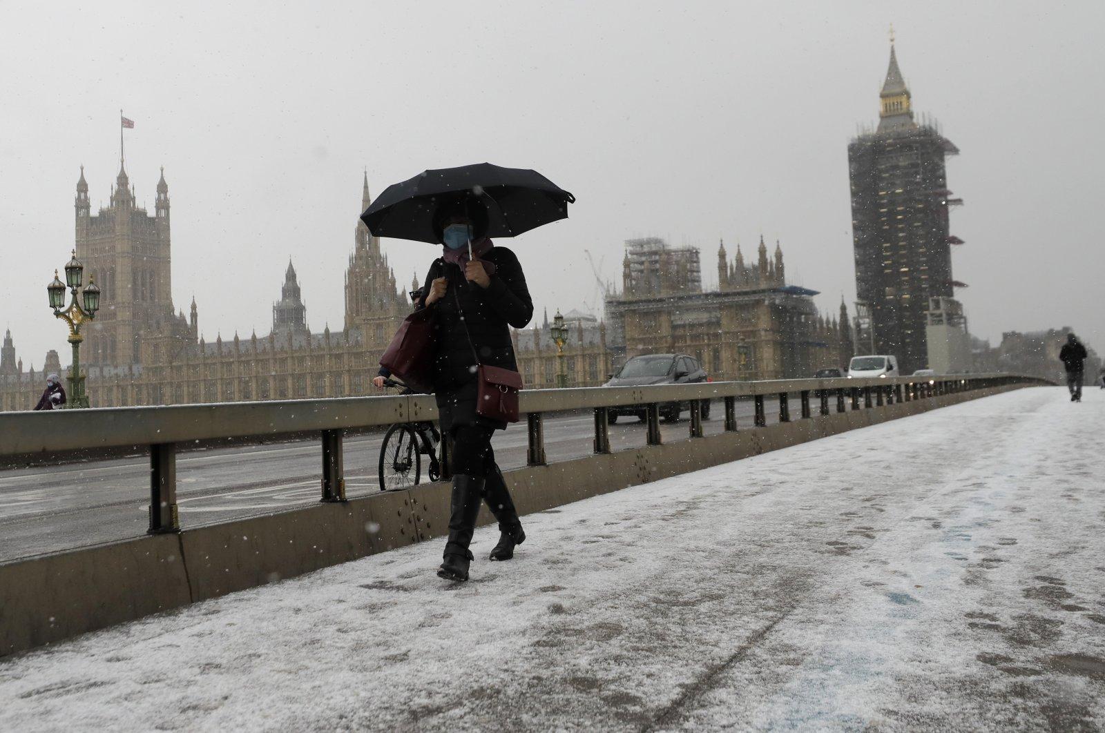 A woman walks over Westminster Bridge as temperatures dropped below freezing during the third coronavirus lockdown in London, England, Feb. 9, 2021. (AP Photo)