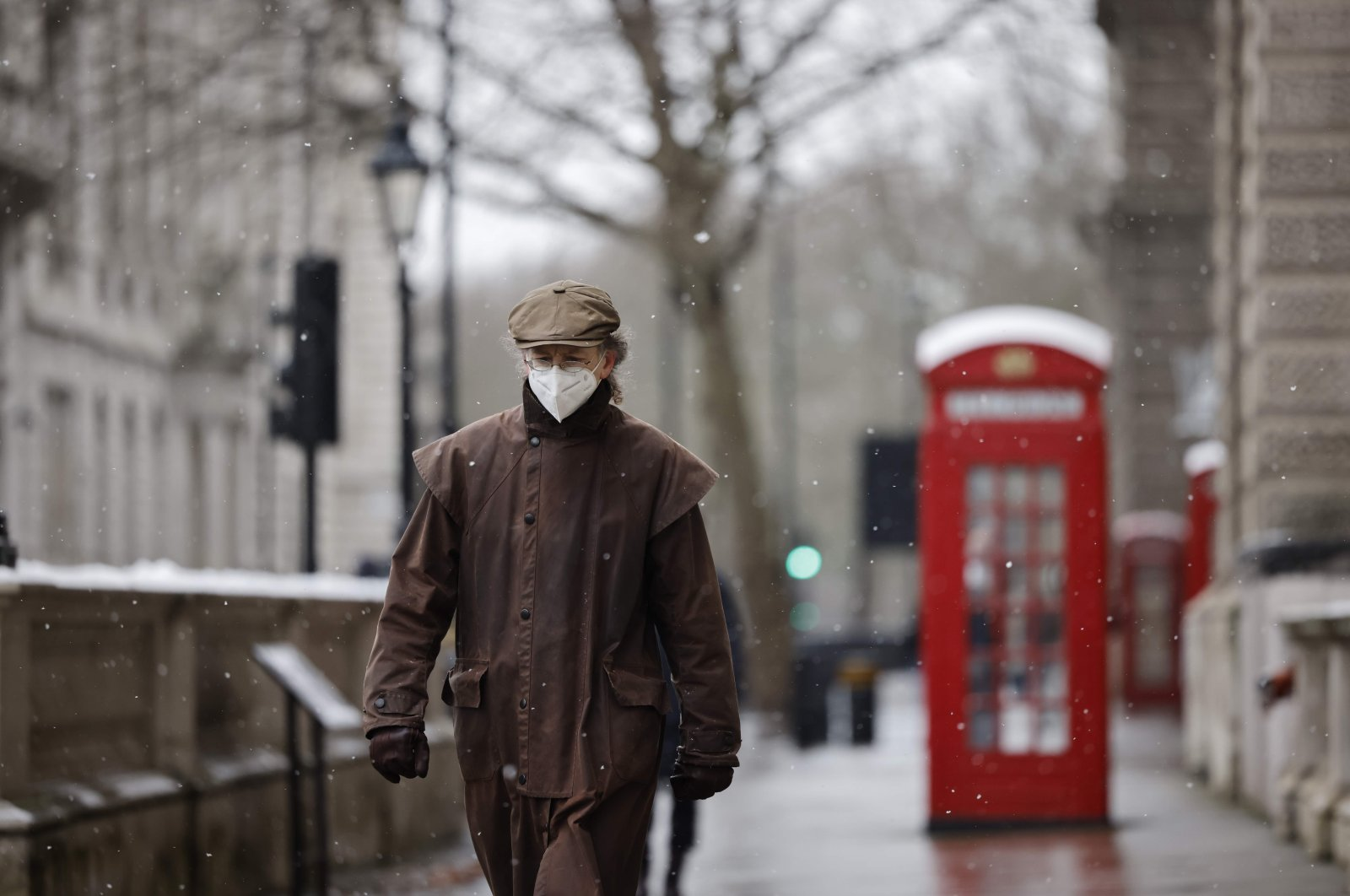 A man wearing a face mask because of the coronavirus pandemic walks in the street in London on Feb. 8, 2021. (AFP Photo)