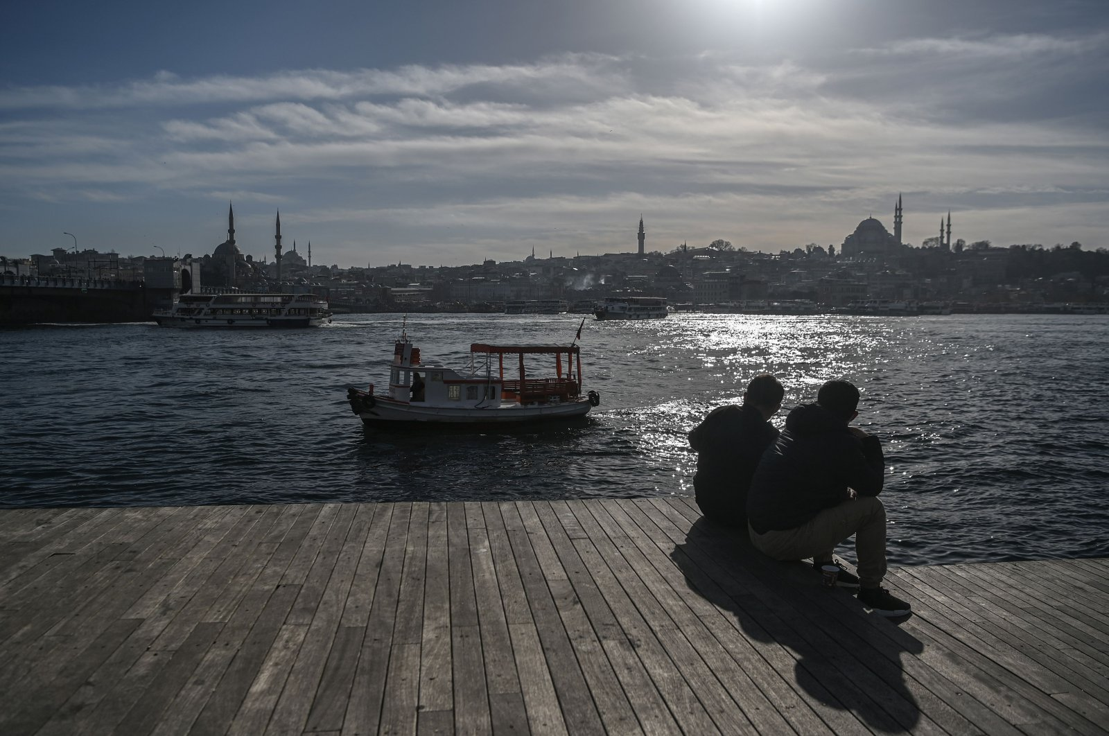 Two men sit next to the shore of the Golden Horn, with the Süleymaniye Mosque in the backround, near Karaköy port, in Istanbul, Turkey, Feb. 10, 2021. (AFP Photo)