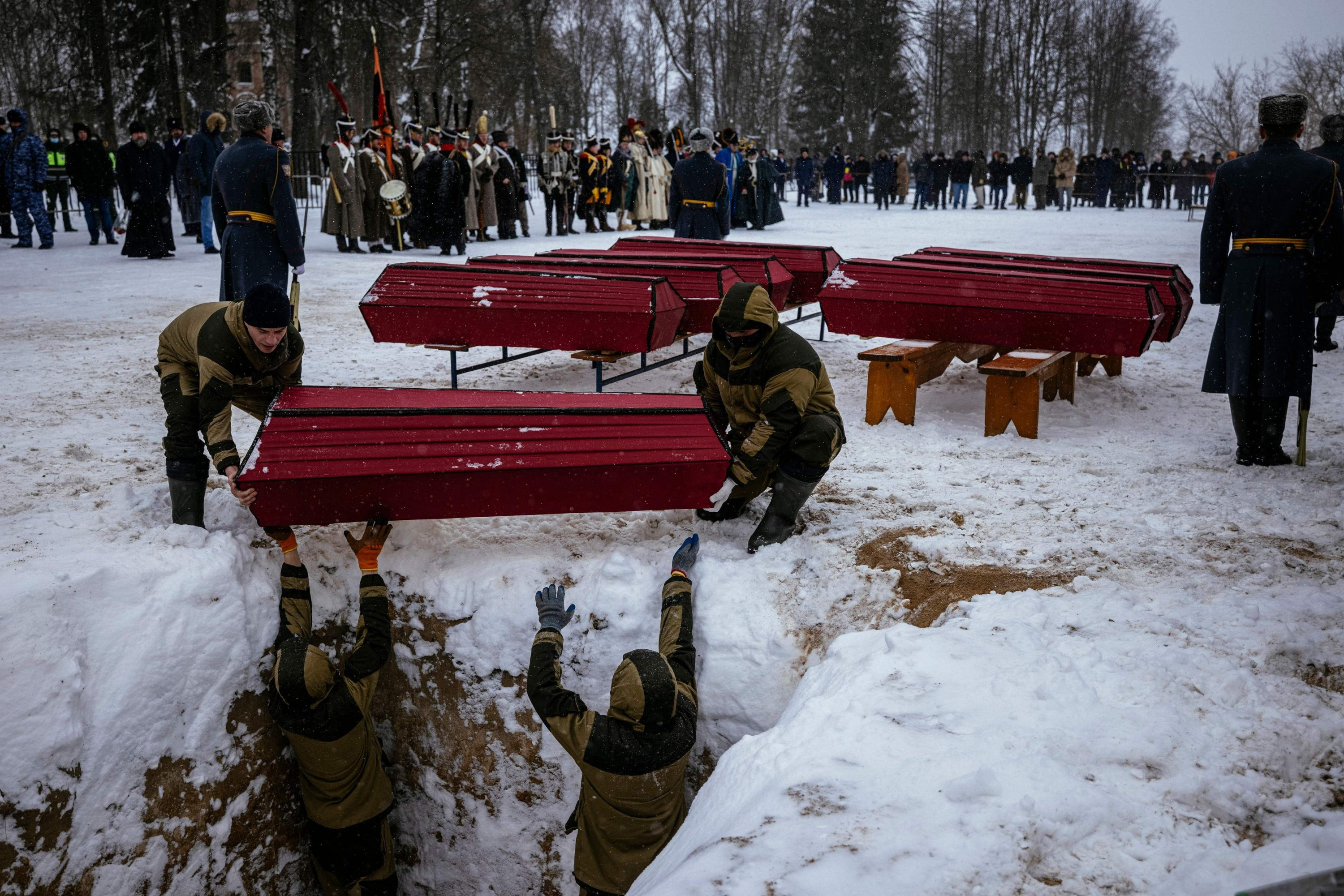 Municipal employees carry coffins containing Russian and French soldiers during a burial ceremony in the western town of Vyazma on Feb. 13, 2021. (AFP)