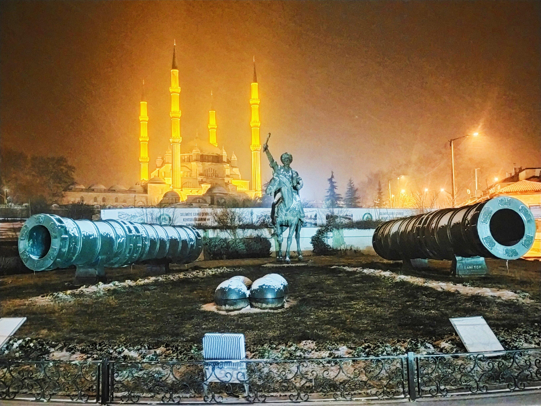 The historic Selimiye Mosque, and the landmark's famous Ottoman architect Sinan's statue, are seen during snowfall in Edirne, northwestern Turkey, Feb. 14, 2021. (IHA Photo)