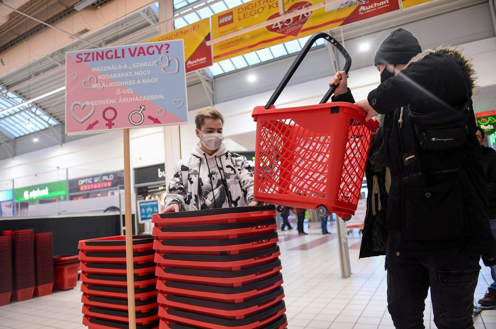 """Two young men pick up their """"single"""" shopping baskets at a French Auchan supermarket in Csomor town, Hungary, on Feb. 12, 202 (AFP Photo)"""