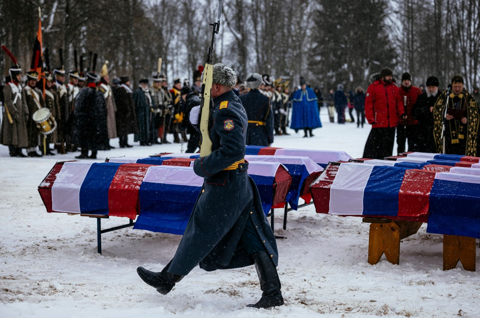 A Russian honor guard passes by coffins containing the remains of Russian and French soldiers during a burial ceremony in the western town of Vyazma on Feb. 13, 2021. (AFP Photo)