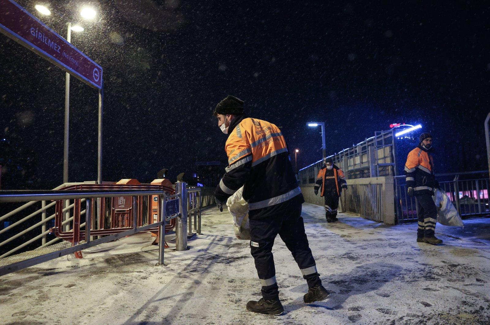 Municipality crews throw salt on overpasses during snowfall at the Cevizlibağ metrobus station in Istanbul, Turkey, Feb. 14, 2021. (AA Photo)