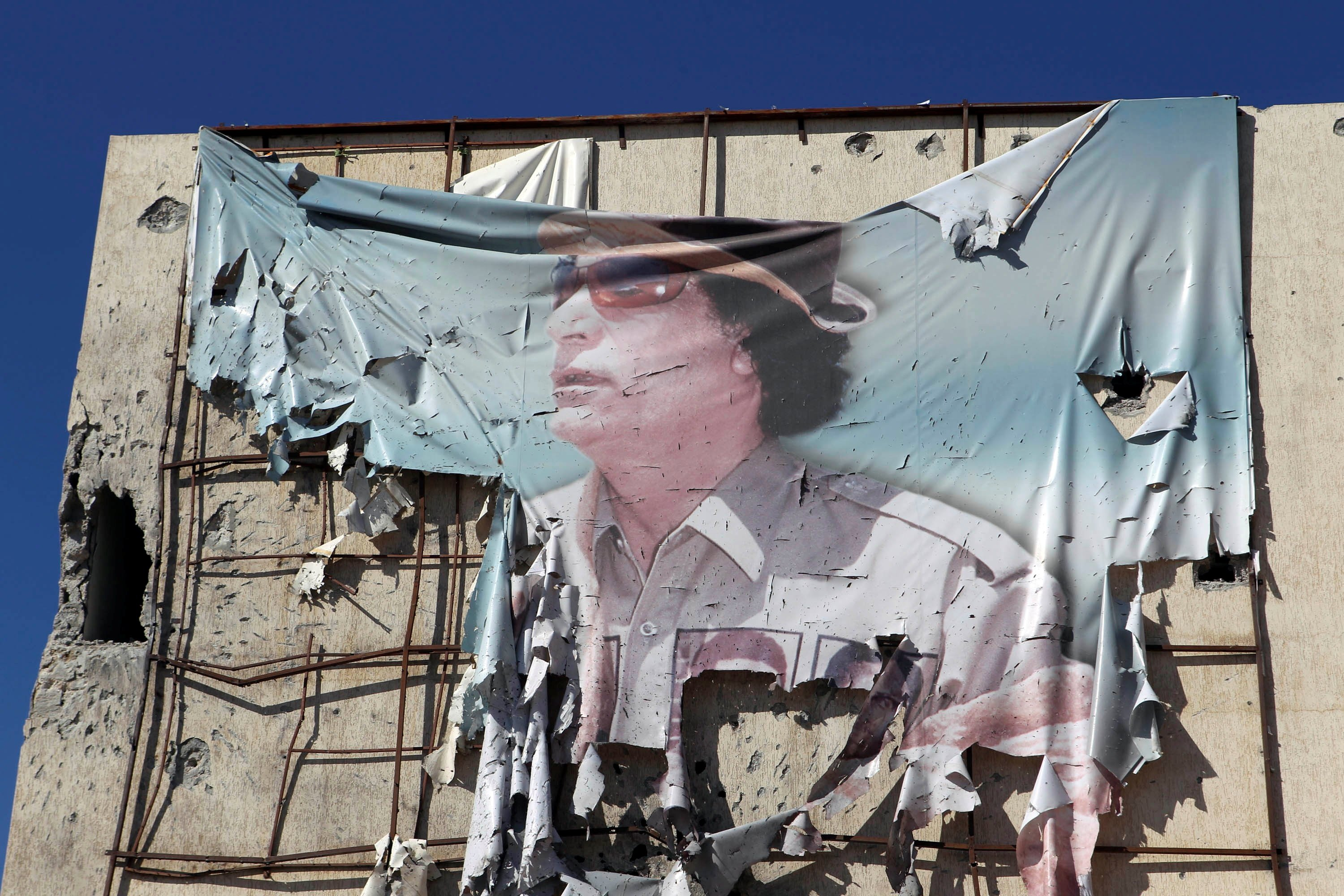 A torn banner showing Muammar Gaddafi on a building during clashes between anti-Gadhafi fighters and Gadhafi forces, Sirte, Libya, Oct. 12, 2011. (Reuters Photo)