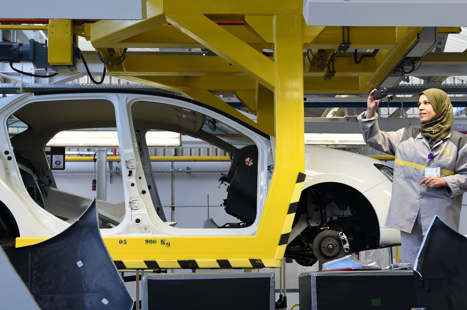 An employee of French carmaker Renault group takes a picture of a car on an assembly line during the inauguration of a new production plant, in Oued Tlelat, Oran, southern Algeria, Nov. 10, 2014. (AFP Photo)