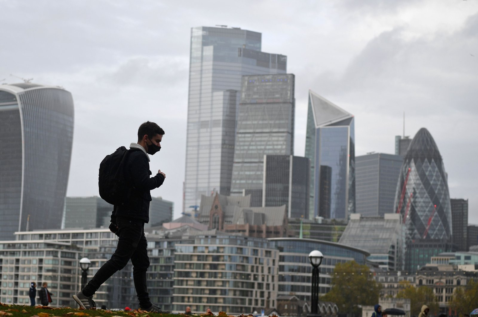 A man walks along the southern bank of the River Thames with the office towers of the City of London in the background, in London, Nov. 1, 2020. (AFP Photo)