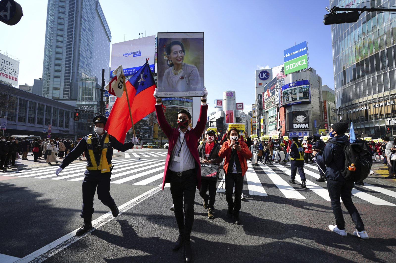 Myanmar people living in Japan and supporters march though Shibuya pedestrian crossings during a protest, Feb. 14, 2021, in Tokyo, Japan. (AP Photo)