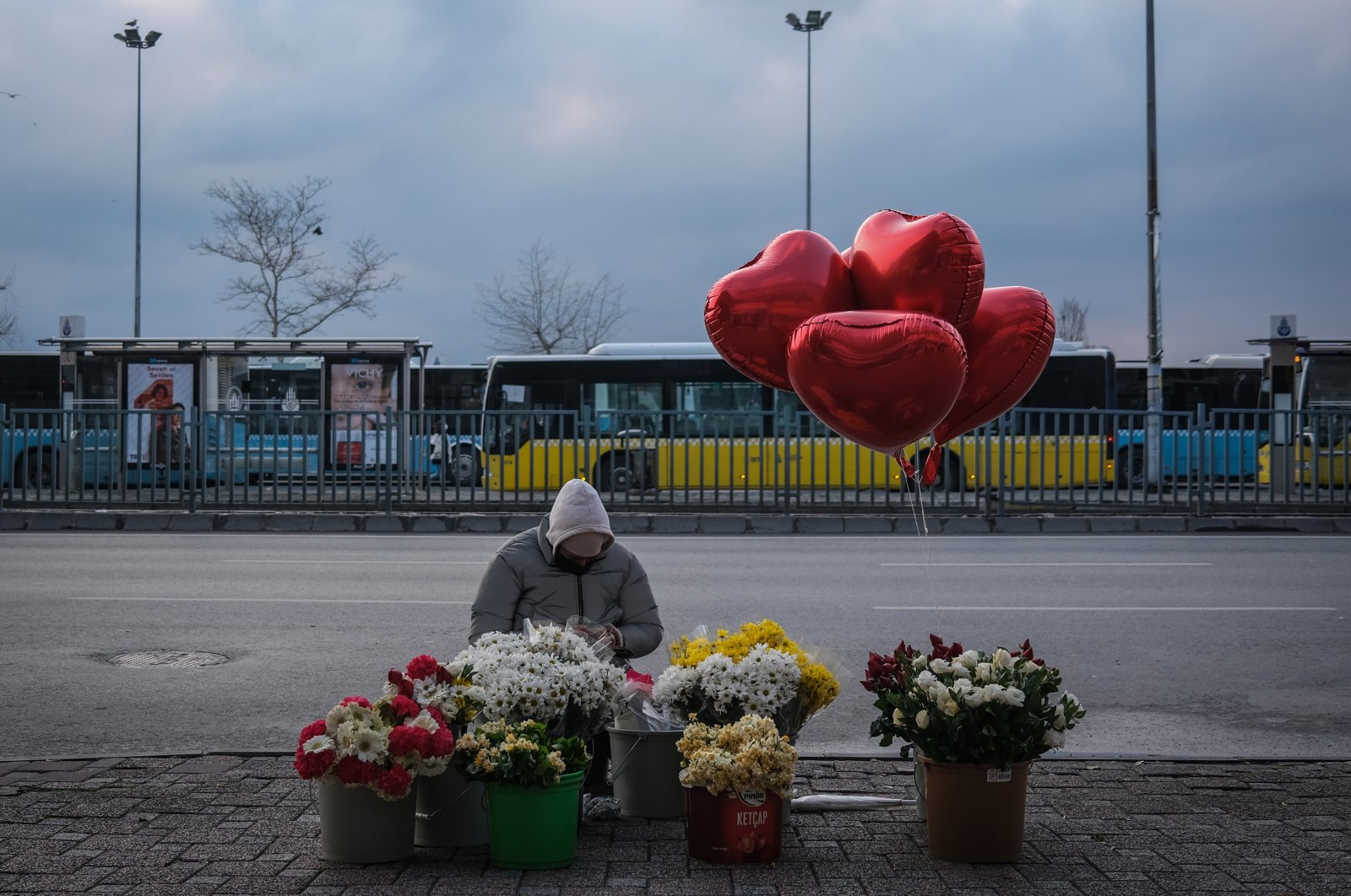 A florist wearing a mask waits for customers on the street before a weekend lockdown in Istanbul, Turkey, Feb. 12, 2021. (EPA Photo)