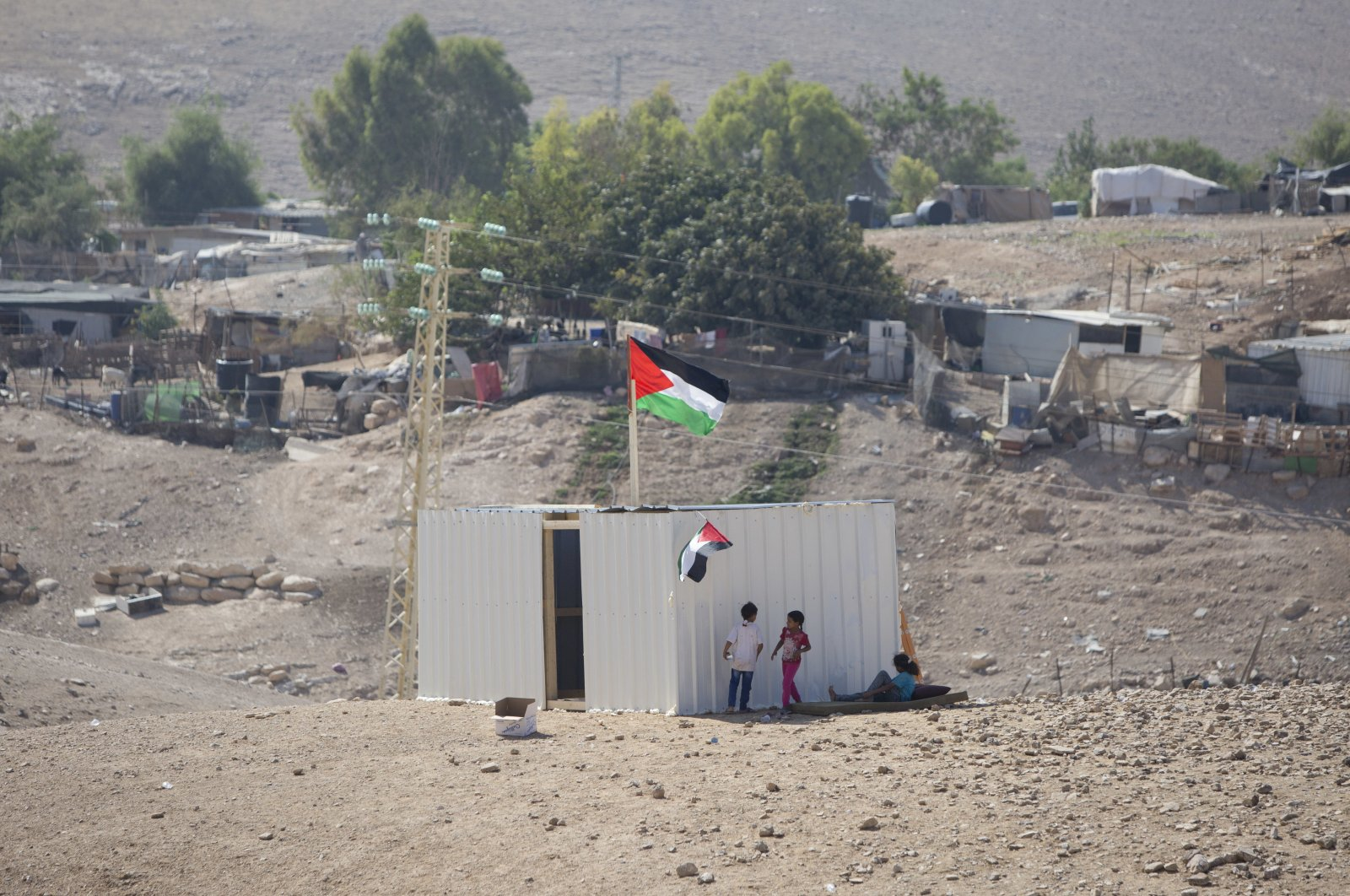 Palestinian girls sit by a newly constructed shed in the West Bank Bedouin community of Khan al-Ahmar, Sept. 11, 2018. (AP Photo)