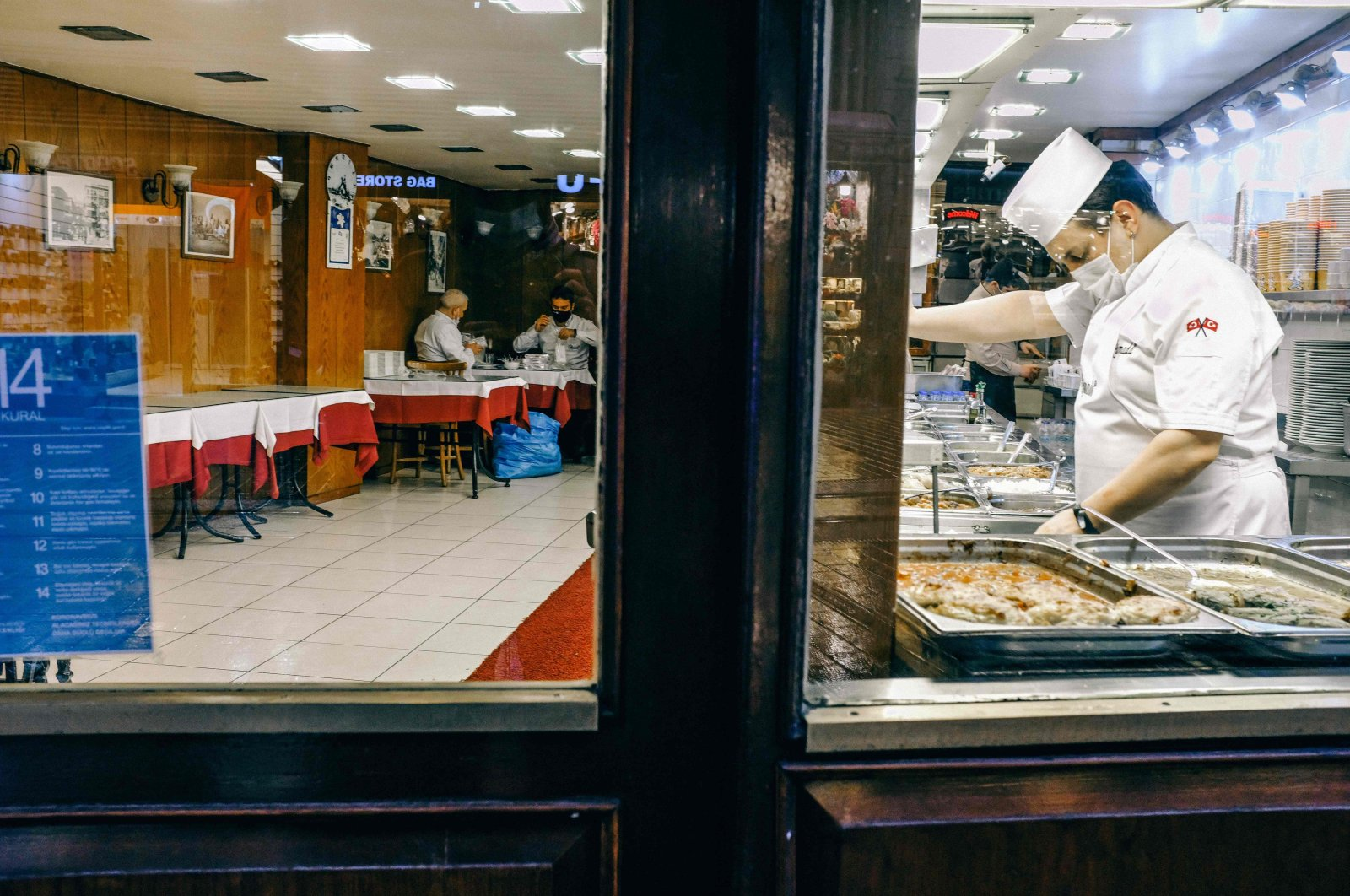 A worker stands behind a counter in a partially empty restaurant on famous Istiklal Avenue in Istanbul, Turkey, Dec. 15, 2020. (AFP Photo)