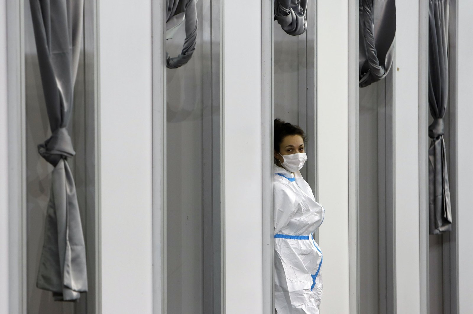 A medical worker wearing protective gear waits for people to receive the COVID-19 vaccine, at Belgrade Fair makeshift vaccination center in Belgrade, Serbia, Feb. 9, 2021. (AP Photo)