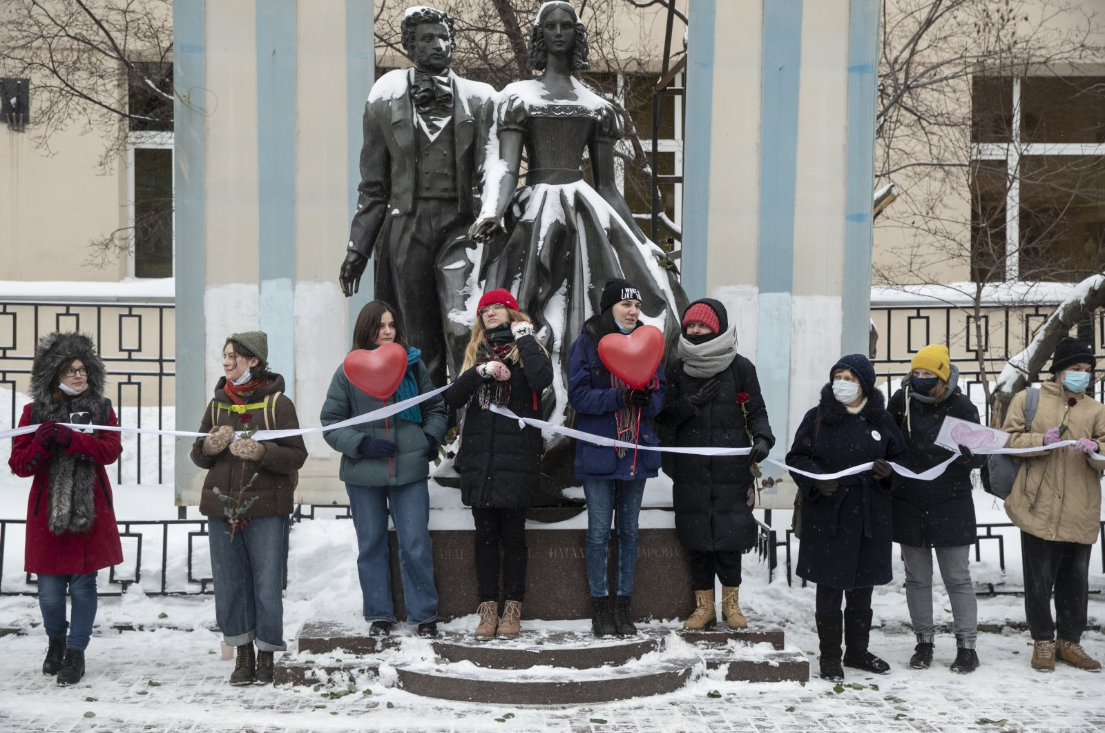 Women hold a white ribbon as they stay in a line during a rally in support of jailed opposition leader Alexei Navalny, and his wife Yulia Navalnaya in Moscow, Russia, Feb. 14, 2021. (AP Photo)