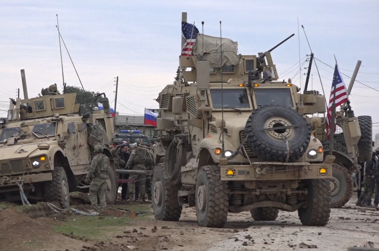 In this frame grab taken from video, people and soldiers gather next to an American military convoy stuck in the village of Khirbet Ammu, east of Qamishli city, Syria, Feb. 12, 2020. (AP File Photo)