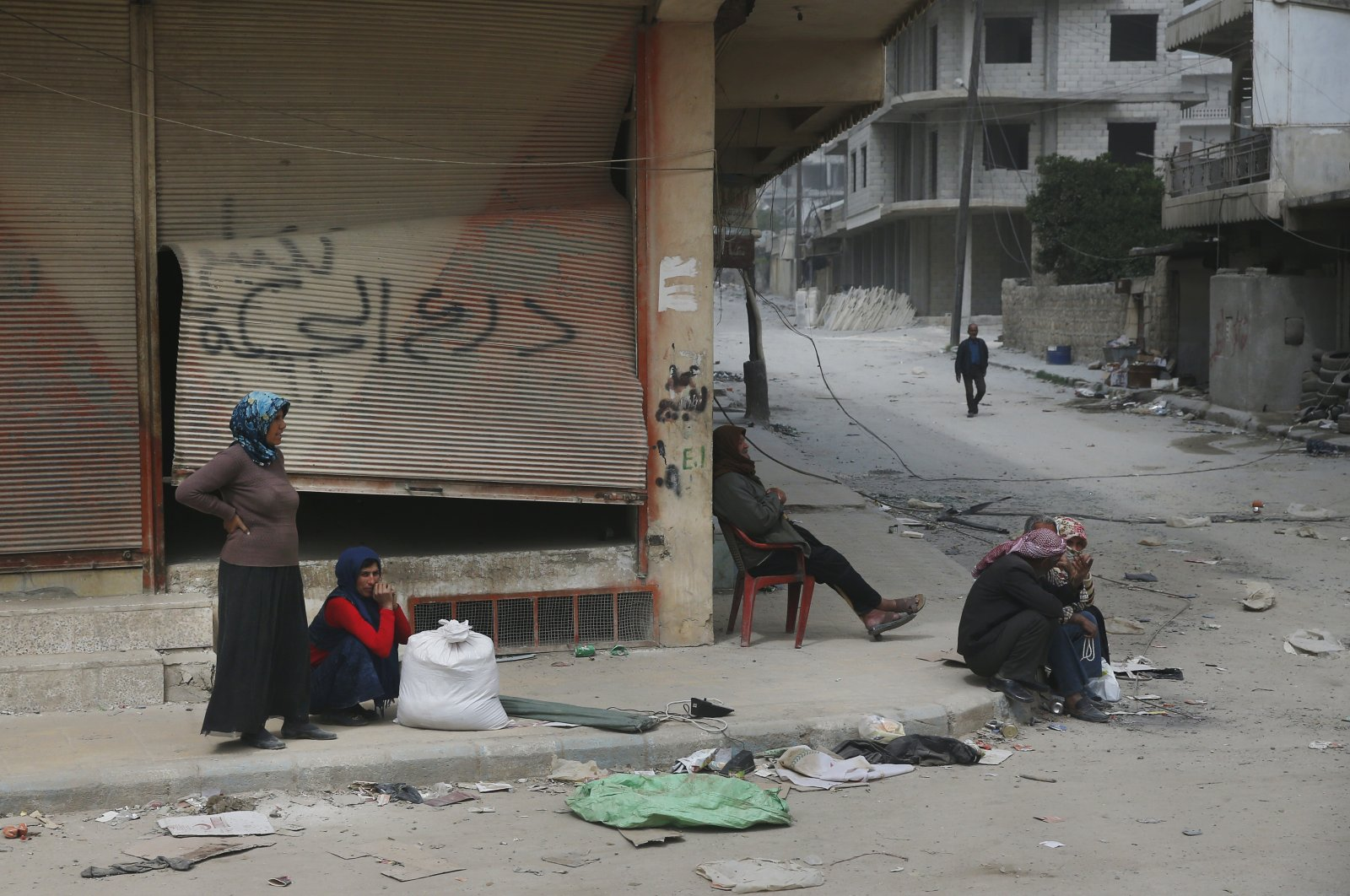 People sit in the damaged streets in the outskirts of the northwestern city of Afrin, Syria, March 24, 2018. (AP File Photo)