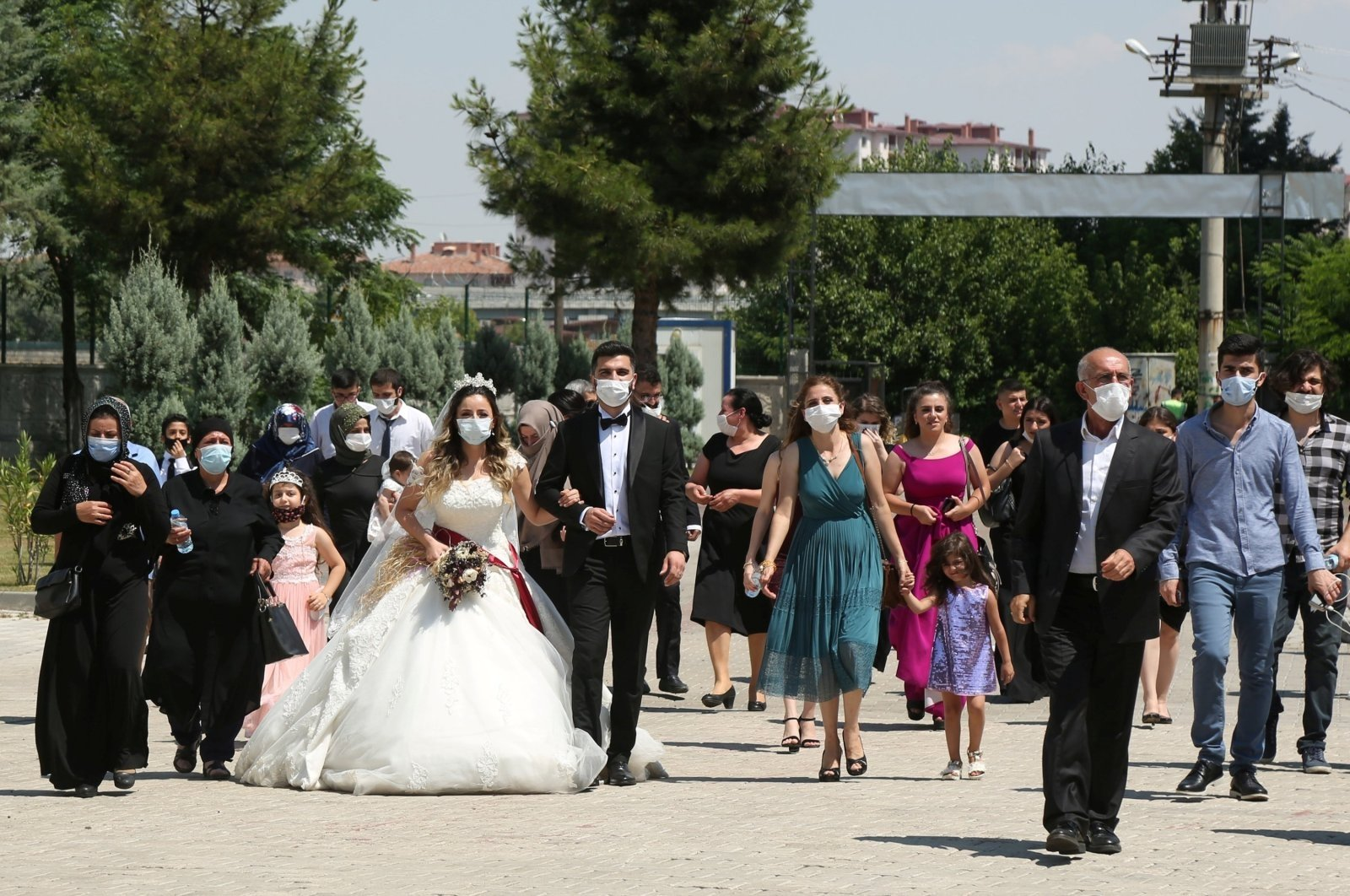 People with face masks walk with a bride and groom following a wedding ceremony in Diyarbakır, southeastern Turkey, July 2, 2020. (Reuters Photo)
