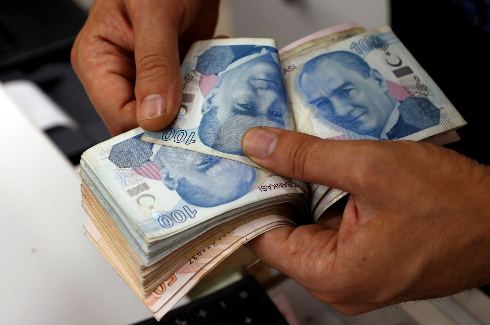 A money changer counts Turkish lira banknotes at a currency exchange office in Istanbul, Turkey, Aug. 2, 2018. (Reuters Photo)