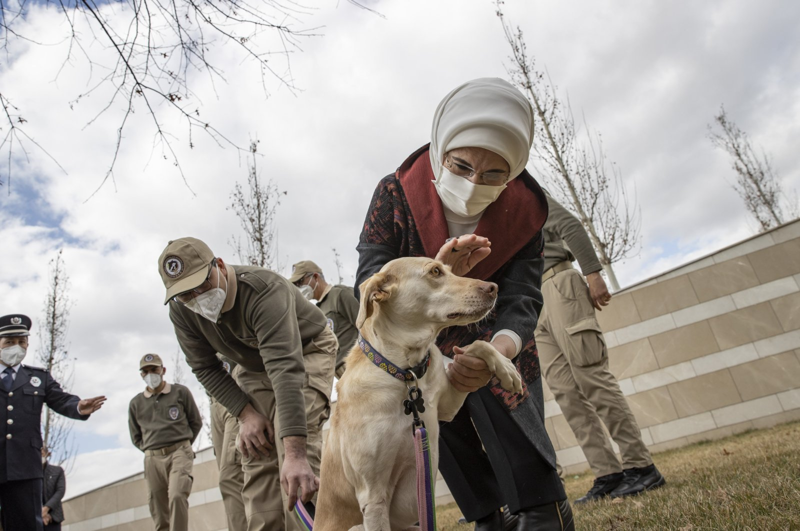"""First lady Emine Erdoğan pets her adopted dog, named """"Leblebi,"""" meaning """"roasted chickpea"""" in Turkish, as she delivers doghouses produced from the waste collected as part of the Zero Waste campaign during the construction of the Presidential Complex, in the garden of the Presidential Library, in the capital Ankara, Turkey, Feb. 10, 2021. (AA Photo)"""