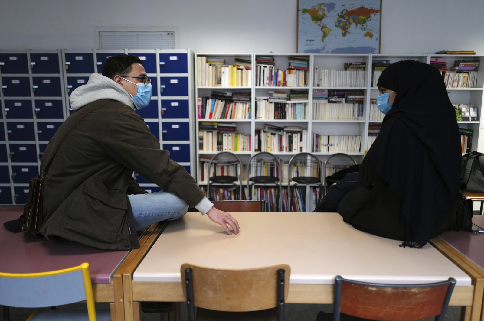 Zinedine Gaid, a teacher of economic sciences and philosophy, (L), talks with Rafika, last name withheld, a student mother, at the Meo High School private college, in Paris, France, Feb. 9, 2021. (AP Photo)