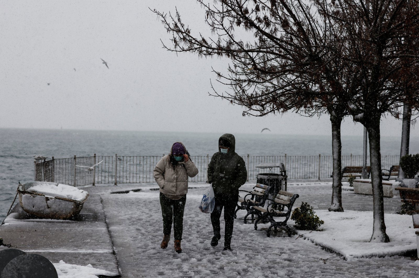 People wearing protective masks walk by the Bosporus, in Istanbul, Turkey, Feb. 14, 2021. (Reuters Photo)