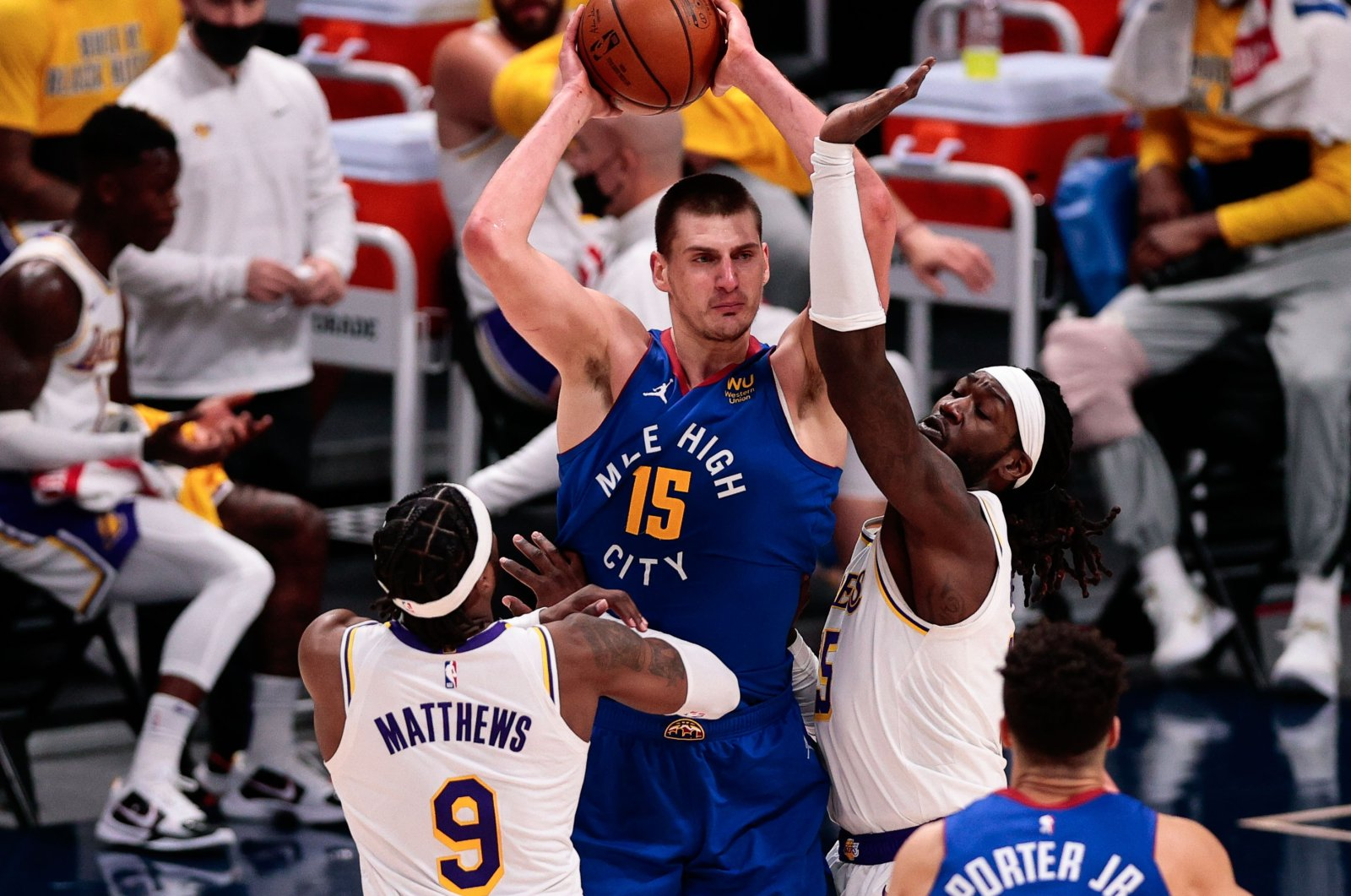Denver Nuggets center Nikola Jokic (C) looks to pass the ball under pressure from Los Angeles Lakers guard Wesley Matthews (L) and center Montrezl Harrell (R) in the third quarter at Ball Arena, Denver, Colorado, Feb 14, 2021. (Reuters Photo)