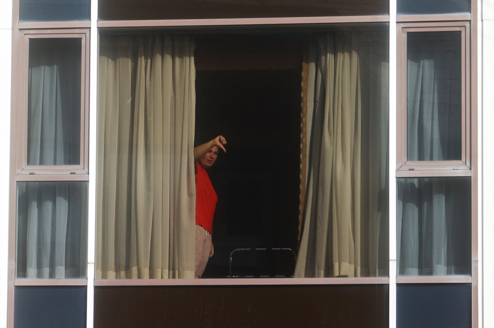 """A woman gestures from the window of the Radisson Blu Hotel at Heathrow Airport, as Britain introduces hotel quarantine program for arrivals from a """"red list"""" of 30 countries, in London, Britain, Feb. 15, 2021. (Reuters Photo)"""