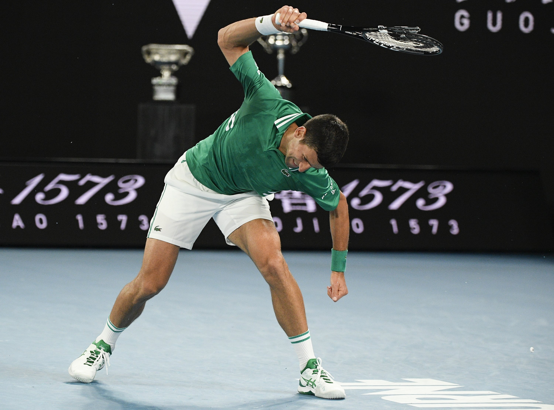 Serbia's Novak Djokovic smashes his racket during his quarterfinal match against Germany's Alexander Zverev at the Australian Open tennis championship in Melbourne, Australia, Feb. 16, 2021. (AP Photo)