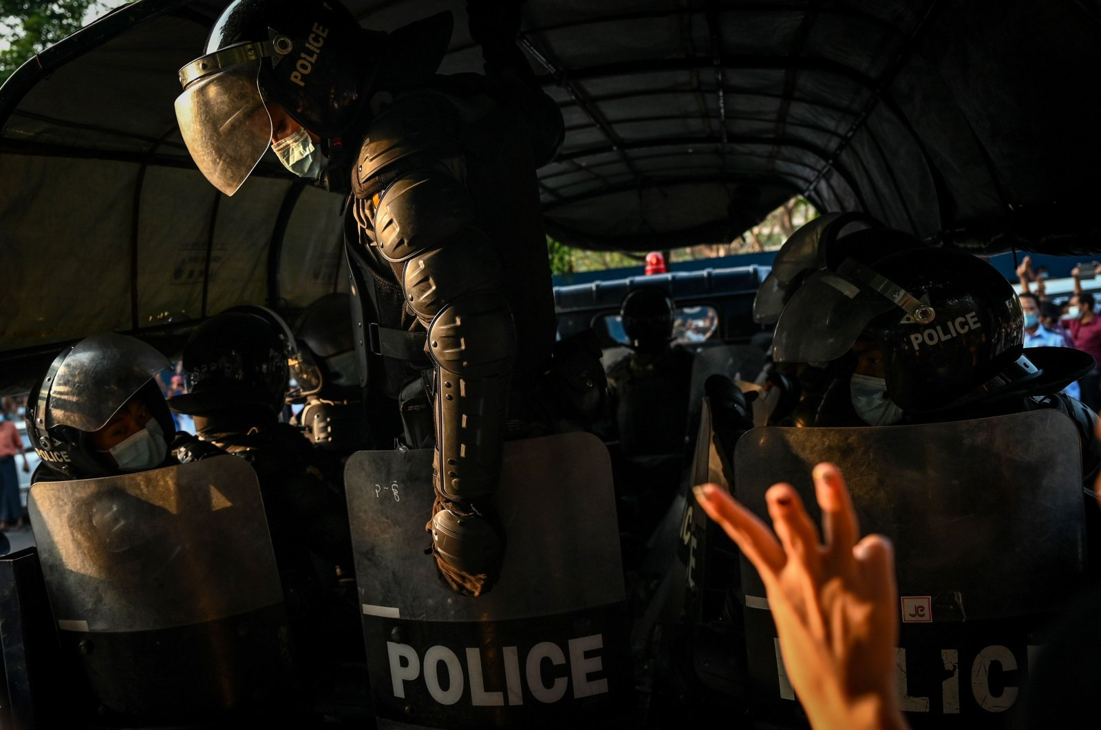 A protester demonstrating against the military coup gives the three-finger salute as police retreat from the headquarters of the National League for Democracy (NLD) in Yangon on Feb. 15, 2021. (AFP Photo)