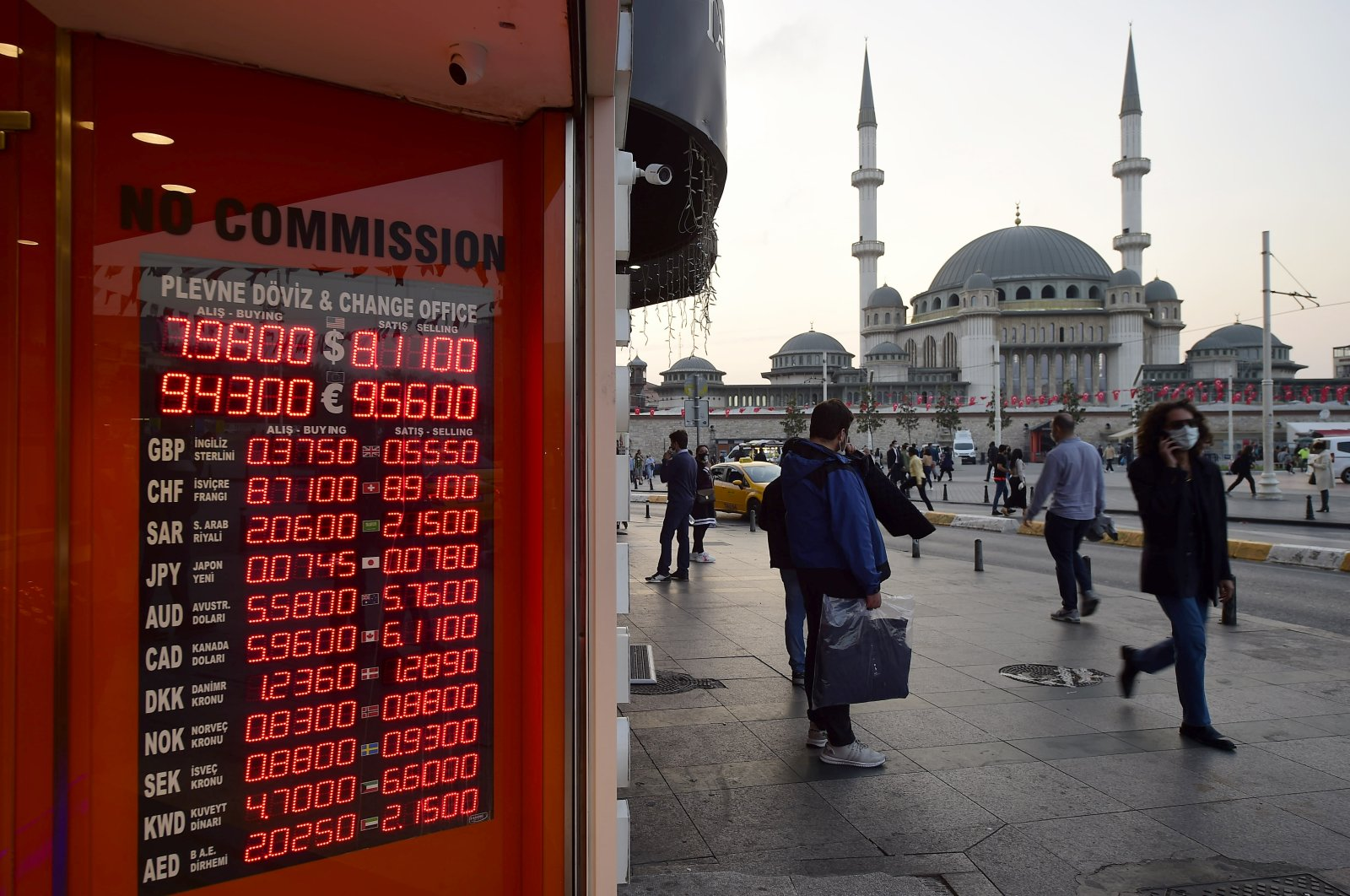 People stand outside an exchange office in the landmark Taksim Square, in Istanbul, Turkey, Oct. 26, 2020. (AP Photo)