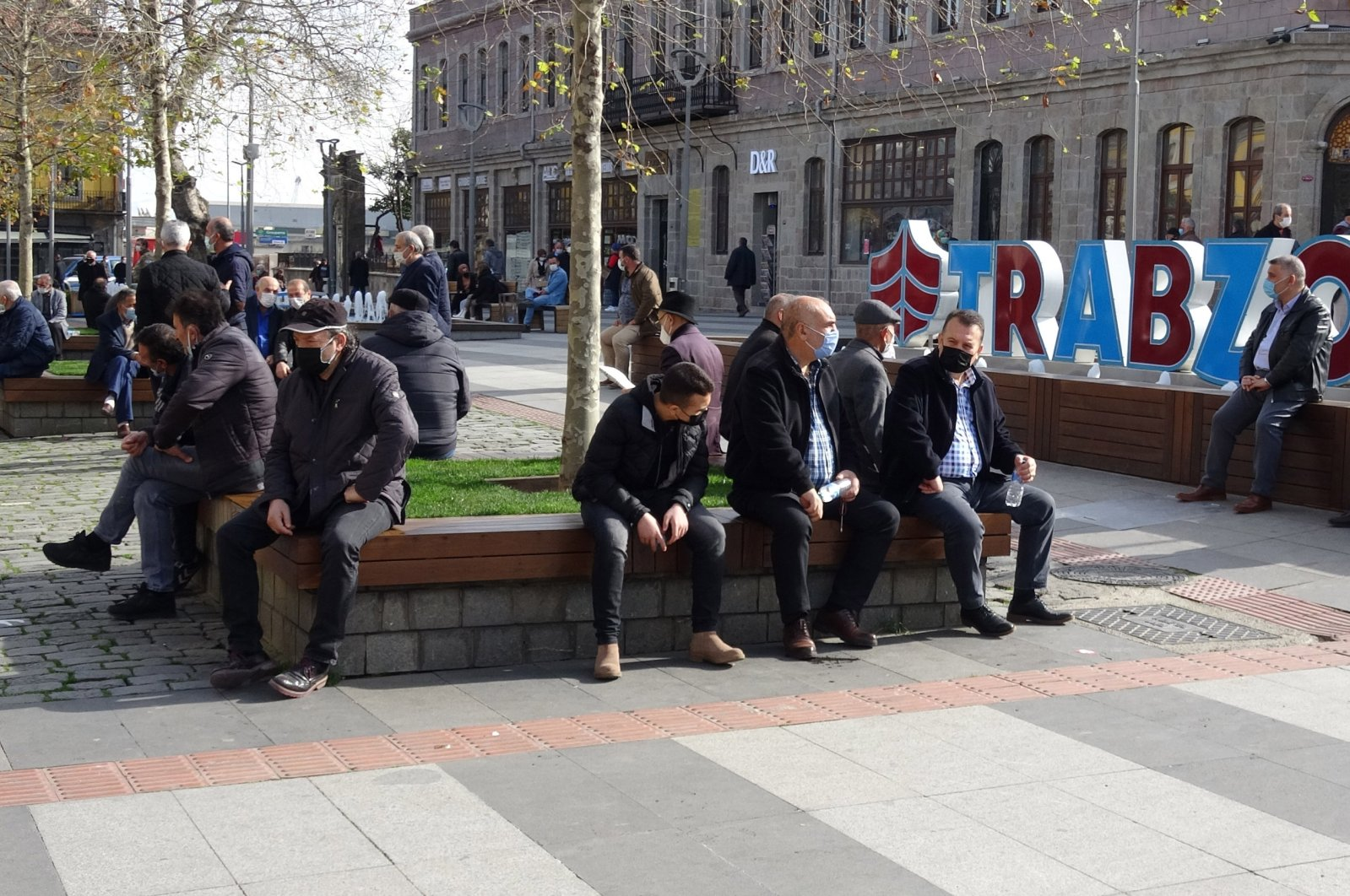 People wearing protective masks sit on benches, in Trabzon, northern Turkey, Feb. 16, 2021. (DHA PHOTO)