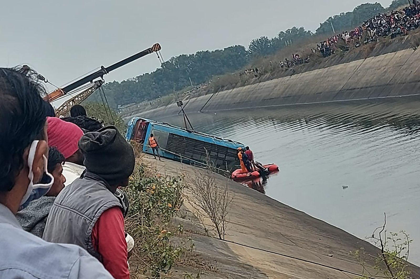A bus that fell into a canal is pulled out in Sidhi district, in the central Indian state of Madhya Pradesh, Feb. 16, 2021. (AP Photo)