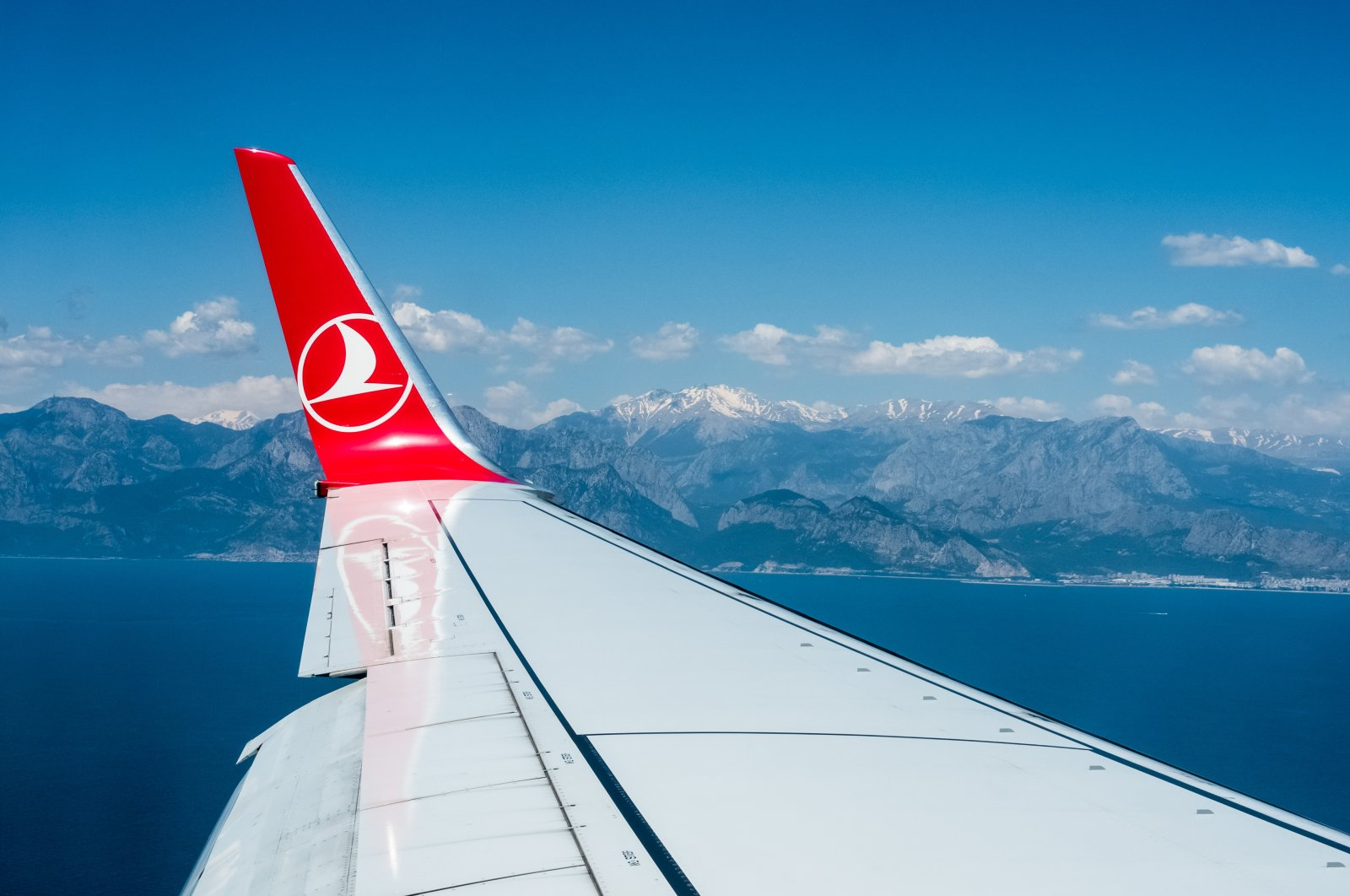Mountains with snowy peaks seen from the window of the Turkish Airlines aircraft in this file photo from May 2019, Antalya, Turkey. (Shutterstock Photo by Tatiana Zolotareva )
