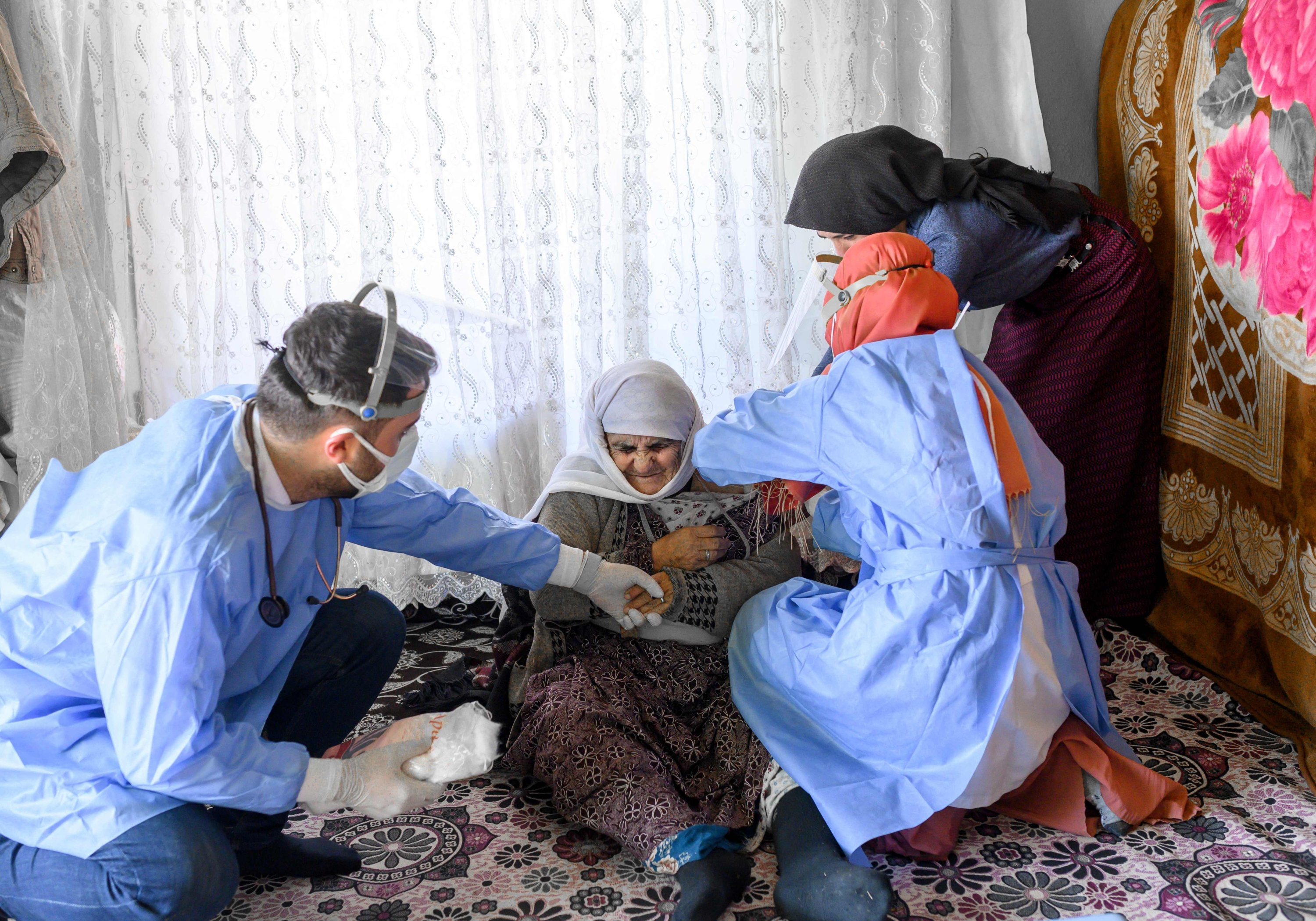 Berfo Arsakay (C), 101 years old, receives a COVID-19 vaccine from nurse Yıldız Ayten (R) from the Bahçesaray public hospital vaccination team, in the village of Güneyyamaç in Van province, eastern Turkey, Feb. 15, 2021. (AFP Photo)